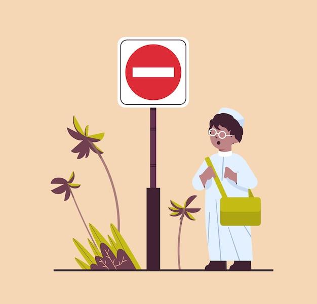 Арабский школьник с рюкзаком, стоящий возле красной остановки, дорожный знак, концепция безопасности дорожного движения, полная длина, векторная иллюстрация