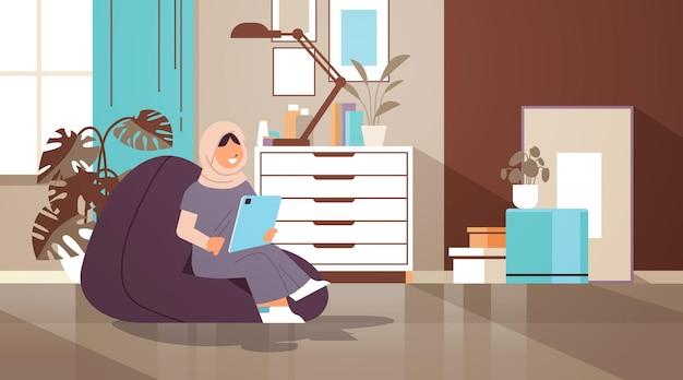Arab schoolgirl using tablet pc arabic girl sitting on beanbag and doing homework education concept living room interior horizontal full length vector illustration