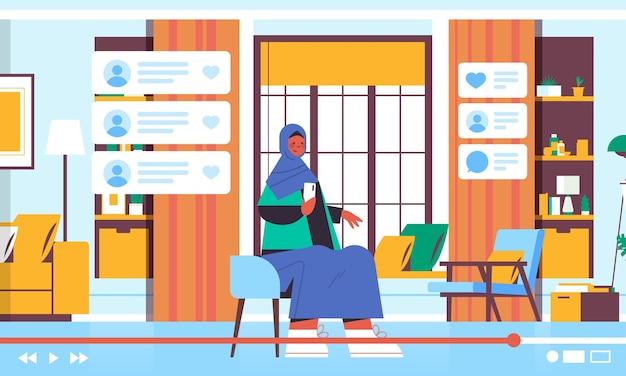 아랍 여성 블로거 스마트 폰 녹화를 사용하여 온라인 비디오 블로그 라이브 스트리밍 블로깅 개념 아랍어 소녀 블로거 거실 인테리어 수평