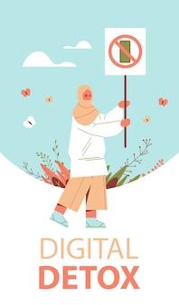 아랍 여자 사용 금지 기호 배너를 들고 교차 아웃 기호 세로 전체 길이 그림에서 스마트 폰 디지털 해독 개념 가제트