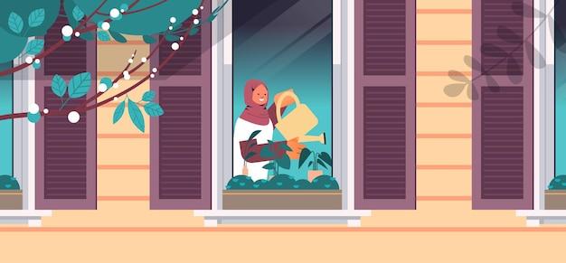 じょうろと植物を注ぐアラブの女性観葉植物の世話をする家の園芸コンセプトの女の子
