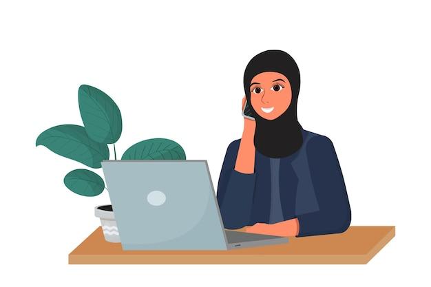 Арабская женщина в хиджабе на рабочем месте разговаривает по телефону и улыбается