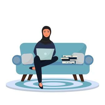 Арабская женщина в хиджабе сидит на диване с ноутбуком и стопкой книг