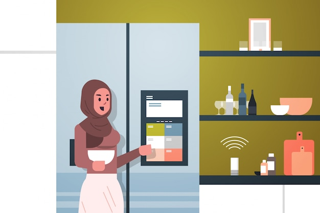 Arab woman touching refrigerator screen with smart speaker voice