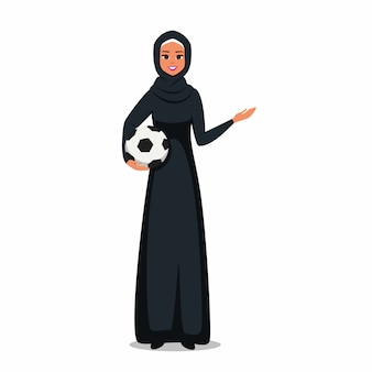 Arab woman wearing hijab holds a soccer ball and showing at something with hand.