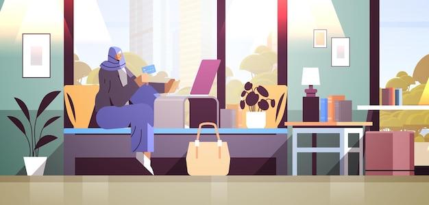 노트북 온라인 쇼핑 개념 거실 내부 수평 전체 길이 벡터 일러스트를 사용하여 신용 카드를 가진 아랍 여성