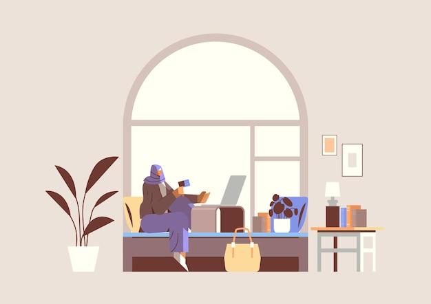 노트북 온라인 쇼핑 개념 거실 내부 수평을 사용하여 신용 카드를 가진 아랍 여성