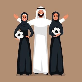 Арабские молодые женщины и арабский мужчина, стоящий вместе с футбольным мячом в руках