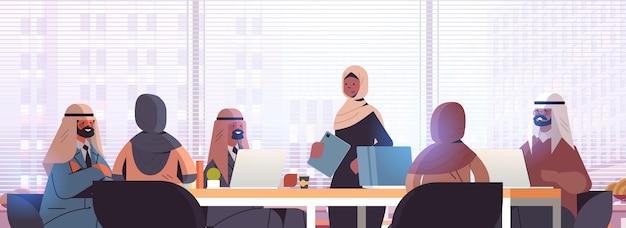 ラウンドテーブルでの会議会議中に議論するアラビアのビジネスマングループ成功したチームワークの概念現代のオフィスインテリア横長の肖像画イラスト