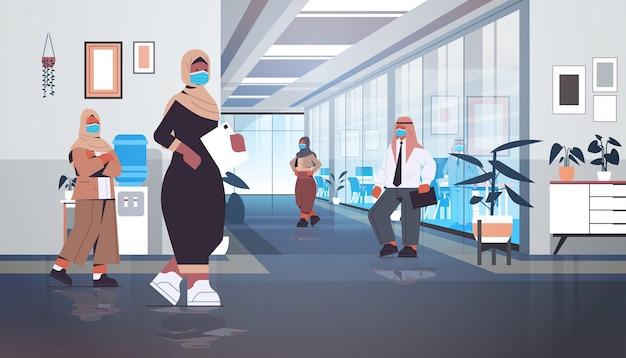 Арабские бизнесмены в защитных масках держатся на расстоянии, чтобы предотвратить пандемию коронавируса арабские коллеги стоят в коридоре офиса в полный рост