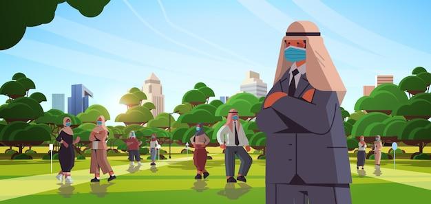 コロナウイルスパンデミックcovid-19検疫の概念を防ぐために保護マスクを身に着けているアラビアのビジネスマン屋外の街並みの背景の水平方向の図を歩くアラブのビジネスマン