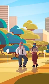コロナウイルスパンデミックcovid-19検疫の概念を防ぐために保護マスクを身に着けているアラビアのビジネスマン屋外の街並みの背景の完全な長さの垂直図を歩くアラブのカップル