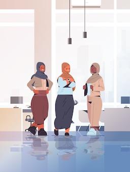 成功した女性のチームのコンセプトオフィスインテリア全長垂直イラストと一緒に立っているアラブのビジネスマンとの会議中に議論するアラビアのビジネスウーマン
