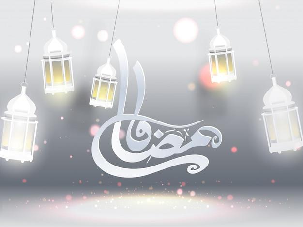 Arabic calligraphy of ramadan kareem and hanging illuminated lan