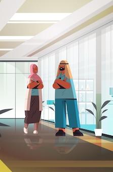 アラビア語の医師は、均一に立って一緒に立っている男性女性医療専門家が会議中に話し合う医学ヘルスケアコンセプトクリニックインテリア垂直全長ベクトルイラスト