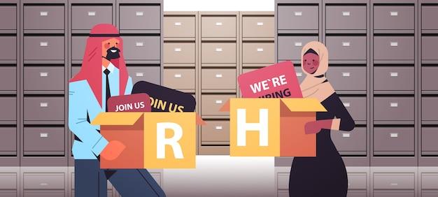 アラビア語の人事マネージャーは、段ボール箱を保持しているカップル人事募集コンセプトファイリングウォールキャビネットデータアーカイブストレージインテリア水平ポートレートベクトルイラスト