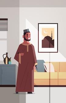 Arabic man in traditional clothes celebrating ramadan kareem holy month modern living room interior flat vertical full length