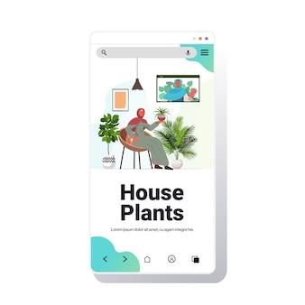 ビデオ通話スマートフォン画面コピースペース中に仮想会議を持っている観葉植物の女の子の世話をするアラビア語の女性