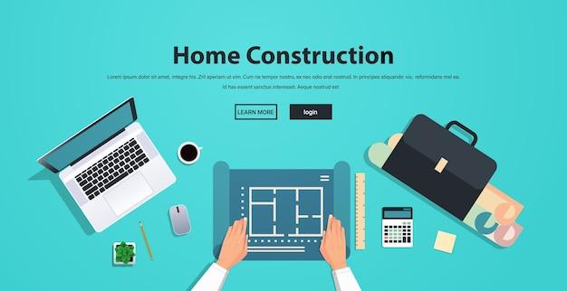 建物の設計図の建設に取り組んでいる建築家コンセプト職場デスクトップアングルビューコピースペース