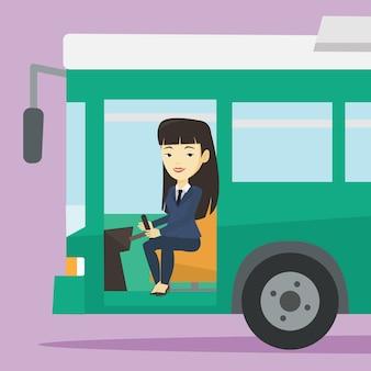 ステアリングホイールに座っているアジアのバスの運転手。