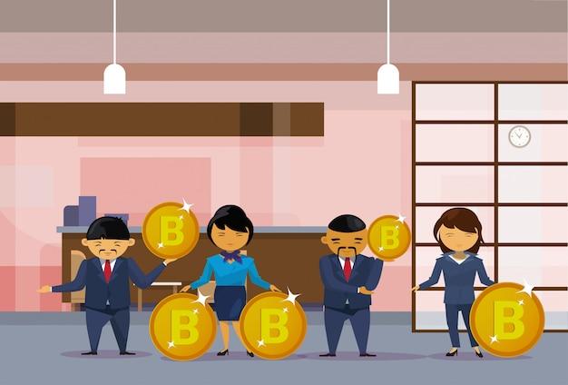 Группа азиатских деловых людей держит монеты биткойнов