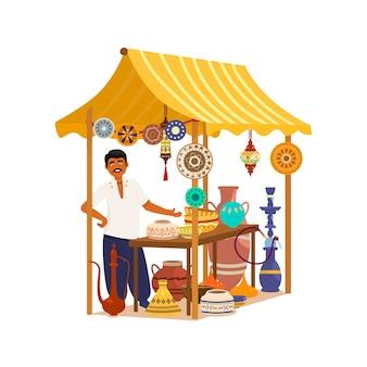 Азиатский мужчина стоит возле уличного магазина, предлагающего традиционные товары и ремесла