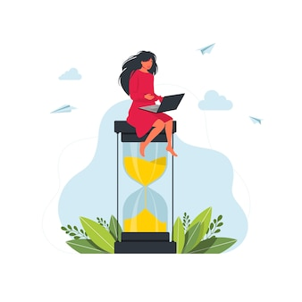 모래시계 시간 관리 개념에 앉아 노트북 작업을 하는 매력적인 여자. 멀티태스킹, 생산성, 시간 관리 개념입니다. 모래 시계에 앉아 있는 여자.생산적인 작업입니다. 시간 관리