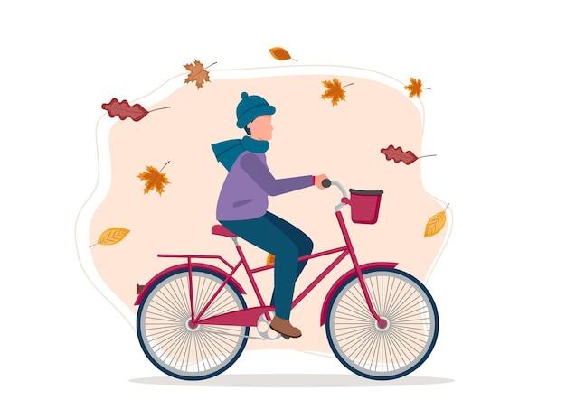 秋の背景。漫画の若い男は自転車に乗る。健康的な生活様式。エコ輸送。