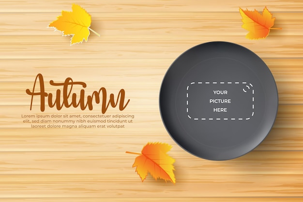 Autumn background with realistic black plate over wooden board