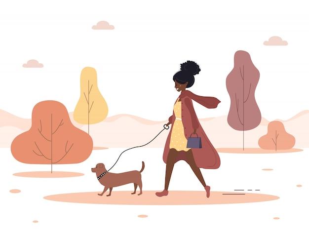 秋の背景。若いアフリカ人女性は森の中を犬と一緒に歩きます。ダックスフントまたはプードルと茶色のコートのコンセプトハッピーガール。フラットスタイルのイラスト。