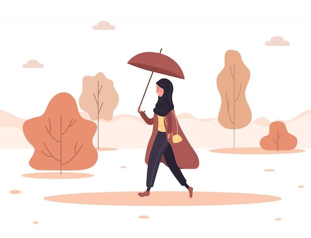 Осенний фон. молодая арабская женщина в хиджабе и пальто с зонтиком идет на работу, в магазин или гуляет в парке. женский персонаж идет под дождем. иллюстрация в плоском стиле.