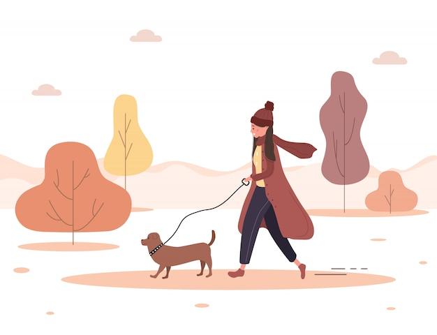 秋の背景。若い女性は森の中を犬と一緒に歩きます。ダックスフントまたはプードルと茶色のコートのコンセプトハッピーガール。フラットスタイルのイラスト。