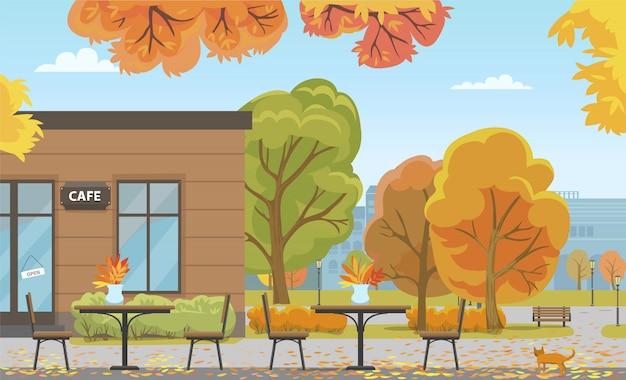 Autumn city park with tables near cafe building
