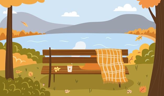 秋の湖の背景格子縞の毛布の山に行くためにベンチコーヒーと秋の公園