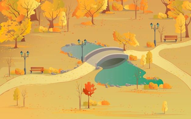 池に架かる橋のある森の秋の風景の小道