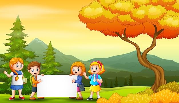 空白の看板を保持している学校の子供たちと秋の風景