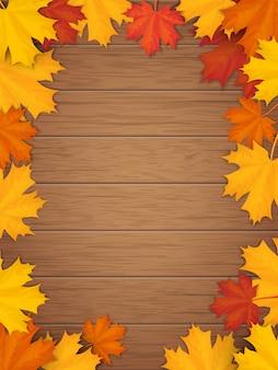 木製の背景に紅葉。落ちたカエデの葉からのフレーム。
