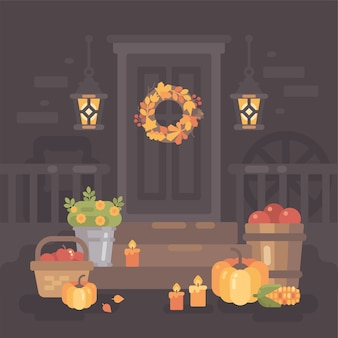 Autumn porch decorated with lanterns, vegetables and leaves.