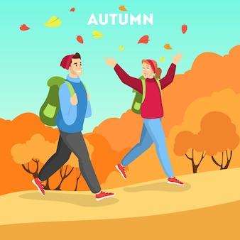 秋の季節、暖かい服装で歩く人