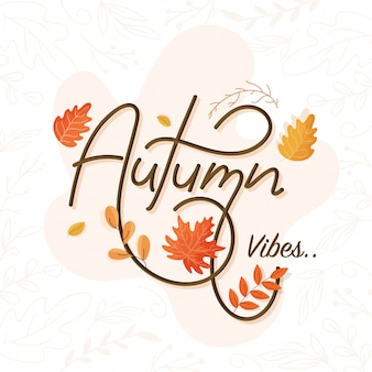 Autumn vibes font on pastel pink and white background decorated with leaves.