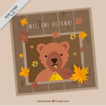 Autumnal card with a bear eating honey