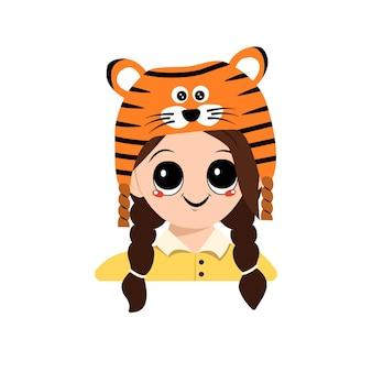 大きな目と広い笑顔の女の子のアバターは、フェストで楽しい顔をした虎の帽子のかわいい子供です...