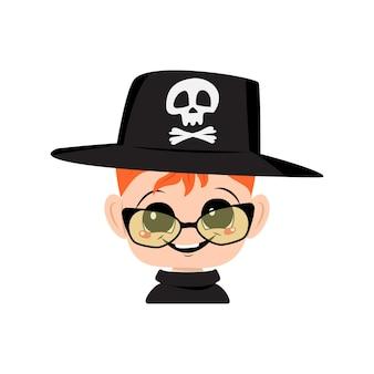 赤い髪、大きな目、眼鏡、頭蓋骨の帽子の広い幸せな笑顔を持つ少年のアバター。お祝いの衣装で楽しい顔をした子供の頭。ハロウィーンパーティーの装飾