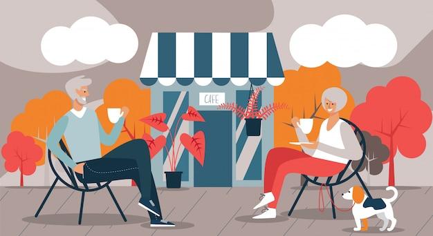 老人男性と女性avd犬のカフェでコーヒーを飲む