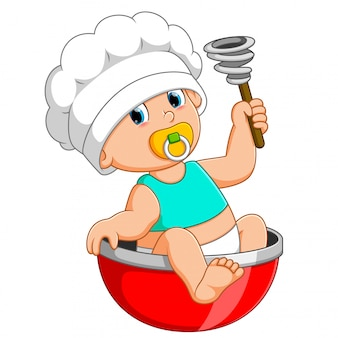 The baby chef is sitting on the red bow and holding manual mixer
