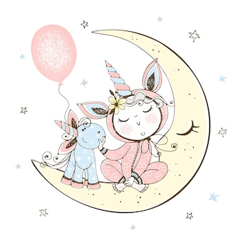 A baby in pajamas is sitting on the moon with his unicorn toy.