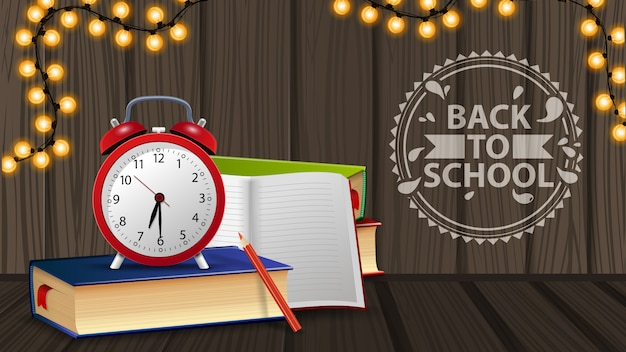 Back to school, alarm clock and books on wooden wall