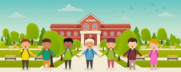 다시 학교로 귀여운 학교 아이들이 학교 앞에 서 있습니다. 학교 앞 마당, 벤치가있는 골목.