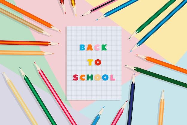 学校に戻る色とりどりの背景に学校のノートと鉛筆教育の概念