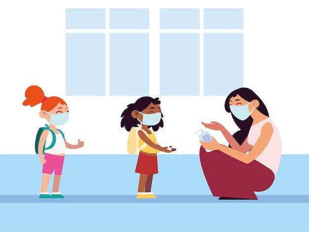 学校に戻って、フェイスマスクのイラストを身に着けている学生の女の子に手指消毒剤を適用する教師
